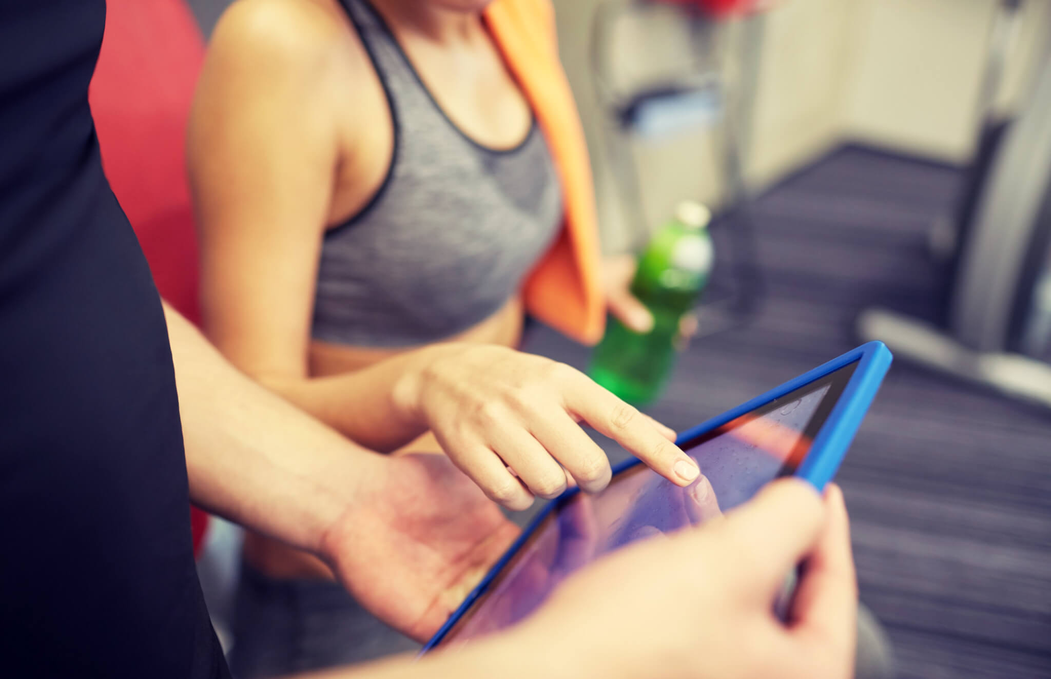 close up of trainer hands with tablet pc in gym